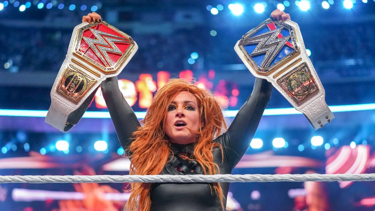 """""""Becky 2 Belts!"""" Becky Lynch proudly holds up her WWE SmackDown and Raw Championship titles."""